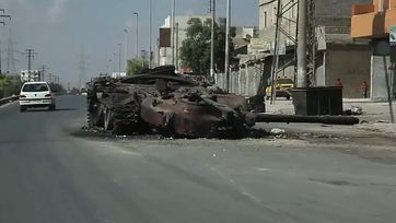 Syrien: A destroyed tank on a road in Aleppo.
