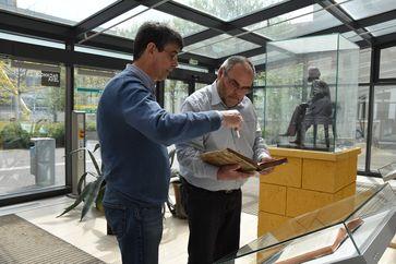 THULB-Werkstattleiter Frank Schieferdecker, li., und Rektor Steffen Teichert mit Newtons Original vor dem ausgestellten Faksimile. Re.die Skulptur von Ernst Abbe, Dauerleihgabe von ZEISS für die EAH