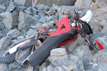 Die Crossmaschine stürzte auf ein Steinfeld unterhalb der Klippe. Der Fahrer lag beim Auffinden auf dem Motorrad. Bild: Polizei