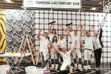 """Geschafft! - Weltrekord im Dauertapezieren. Großer Jubel beim Maler Nationalteam auf der Heimtextil. Bild: """"obs/Deutsches Tapeten-Institut/David Haase"""""""