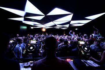 DJ und Tanzende in einem Techno-Club der 2010er Jahre in München