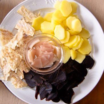 Tvøst og spik. Das schwarze Grindwalfleisch und Speck (in der Schale) wird gerne zusammen mit Trockenfisch (links) und Salzkartoffeln gereicht. Dazu trinkt man traditionell Bier