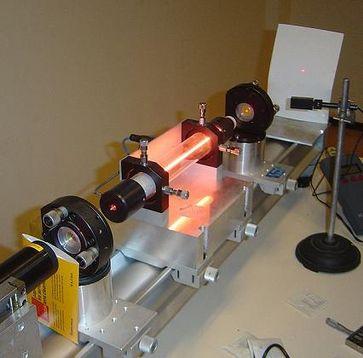 Demonstrationslaser: In der Mitte ist das Leuchten der Gasentladung zu sehen, die das Lasermedium anregt. Der Laserstrahl ist rechts als roter Punkt auf dem weißen Schirm zu erkennen. Bild: de.wikipedia.org /