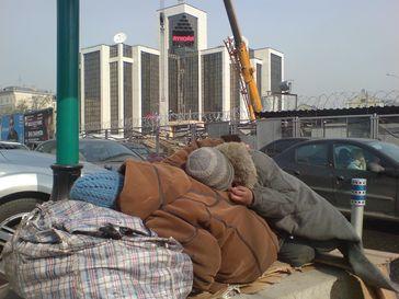 Wohnsitzlose schlafen nahe dem Lukoil in Moskau