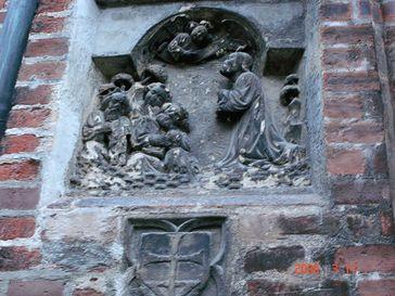 Asylzeichen am Liebfrauendom zu München (Kreuz in einem Schild, unten), unter einer Darstellung der Ölbergszene, die außen an Kirchen Hinweis auf ein Kirchenasyl ist.