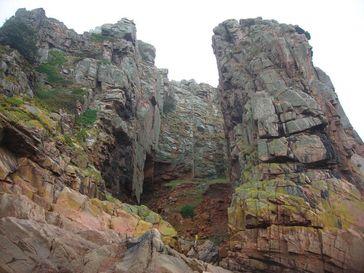 Ansicht der Fundstelle La Cotte de St Brelade auf der Insel Jersey, Großbritannien. Ein Großteil der Knochen stammt aus den Ausgrabungen unter dem Granitbogen links im Bild ist. Quelle: Foto: Geoff Smith, MONREPOS (idw)