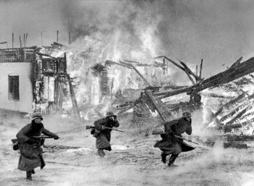 Wehrmachtssoldaten beim Kampf um ein brennendes Dorf