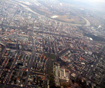 Blick über Offenbach am Main von Süden; im Vordergrund links (senkrecht) die Waldstraße, dahinter (waagerecht) die Bebraer Bahn, im Vordergrund rechts (senkrecht) der Offenbacher Alleenring, im Hintergrund links die Innenstadt und jenseits des Mains Frankfurt-Fechenheim