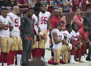Stehende und kniende Spieler der San Francisco 49ers vor einem Spiel im Oktober 2017