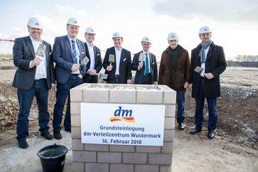 """v.l.n.r.: Joachim Lück (Projektleiter dm-VZ Wustermark), Bürgermeister Holger Schreiber, Heinz Ennen (Geschäftsführung Swisslog GmbH), Christian Bodi (dm-Geschäftsführer für das Ressort Logistik), Albrecht Gerber (Minister für Wirtschaft und Energie Brandenburg), dm-Gründer Götz W. Werner und Martin Dallmeier (dm-Geschäftsführer für das Ressort Finanzen + Controlling). Bild: """"obs/dm-drogerie markt/Peter-Paul Weiler"""""""
