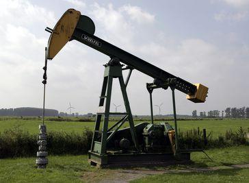 Erdölförderung in Deutschland: Pferdekopf-Pumpe auf dem ehemaligen Erdölfeld Varel. Im Hintergrund drei Windkraftanlagen