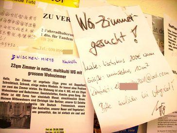 WG-Zimmer-Angebote und -Gesuche an einem schwarzen Brett in Berlin