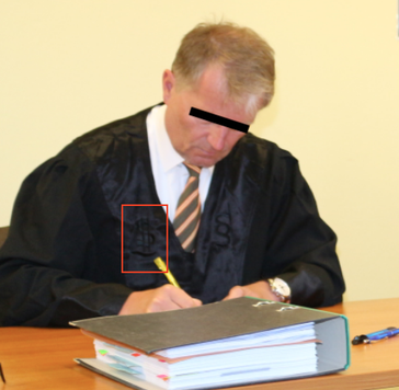 Rechtsanwalt Schmidt mit dem § und $ Zeichen auf der Robe