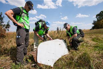 Niederländische und australische Einsatzkräfte untersuchen ein Wrackteil.