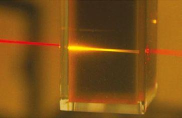 Rotes Licht eines Laserpointers wird beim Durchgang durch die Flüssigkeit des photochemischen Hochkonverters in energiereiches gelbes Licht umgewandelt. Quelle: Foto: University of Sydney, Australien (idw)