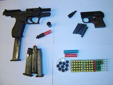 Schreckschusspistolen Walther P99 (l.) und Röhm Mod. 3S (r.), Patronen (blau = CN, gelb = CS, rot = Pfeffer und sonstige Reizstoffe, grün = Platz) und Signalmunition