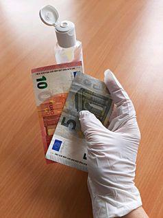 Geldscheine in behandschuhter Hand und Desinfektionsmittel Bild: Polizei
