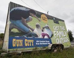 Gun-City-Werbung: Kinder visieren mit Waffe Ziel an.