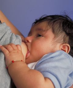 Ein Säugling wird an der Mutterbrust gestillt.