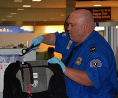 Transportation Security Administration:  TSA officer screening luggage