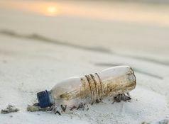 Plastikflasche am Strand: viele Mikroteile im Meer.