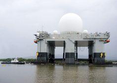 """Das Sea-Based X-Band Radar (SBX) verläßt Pearl Harbor (Hawaii, 31. März 2006). Die SBX Plattform verfügt über sechs 3.6 Megawatt-Dieselgeneratoren. Wenn alle Generatoren laufen, kann die Platform über 20 Megawatt an Wellenleistung abstrahlen. Zum Vergleich; die HAARP-Installation (in Gakona, Alaska – 62°23?33.73""""N 145° 9?2.61""""W) hat 3.6 Megawatt Leistung."""