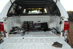 Die Ausrüstung, die zu den Aufnahmen der individuellen Gesänge und neuronalen Signale benötigt wurde, steht im Heck eines Autos in ca. 30 Meter Entfernung zum Nistbaum der Mahaliweber. Quelle: Susanne Hoffmann (idw)