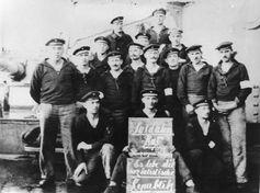 """Matrosen an Deck des Linienschiffs Prinzregent Luitpold mit einer Tafel: """"Soldatenrat Kriegsschiff Prinzregent Luitpold. Es lebe die sozialistische Republik."""""""