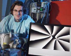 In einem Labor des Instituts für Optik und Quantenelektronik der Friedrich-Schiller-Universität Jena zeigt der Physiker Michael Zürch auf einem Bildschirm sogenannte optische Wirbel, die durch Beschuss von Argon-Gas mit einem Femtosekundenlaser erzeugt werden. Quelle: Foto: Jan-Peter Kasper/FSU (idw)