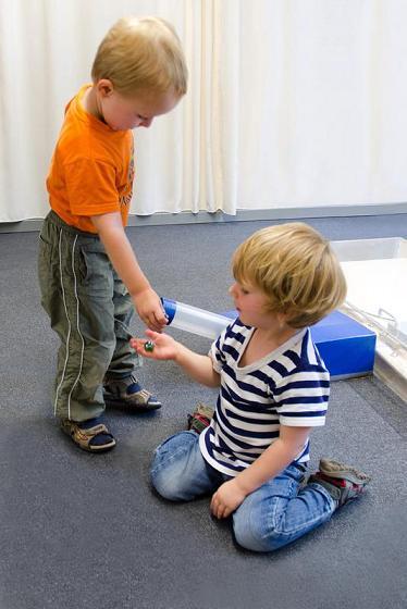 Bereits dreijährige geben einem anderen kind spielzeug ab