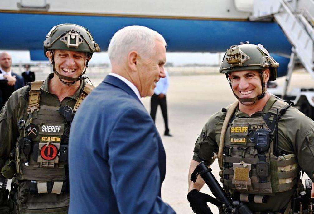 """US-Vizepräsident Mike Pence mit Mitgliedern des Broward County SWAT-Teams am 30. November 2018 in Florida; Der Mann links zeigt einen rot-schwarzen """"Q"""" -Aufnäher, ein Symbol von QAnon."""