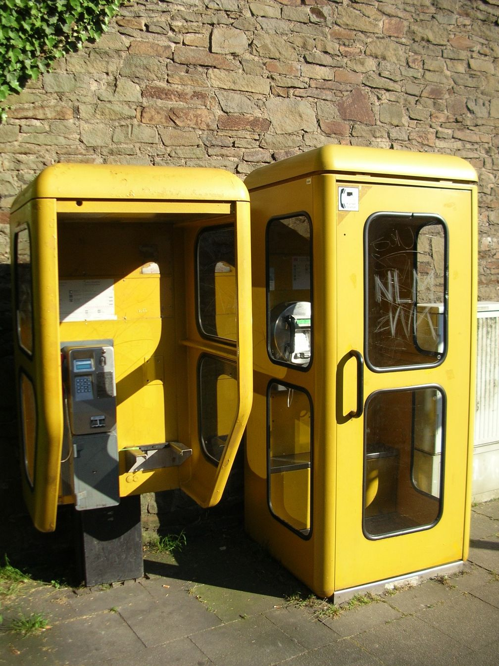 Links eine Telefonhaube TelHb82, auch für Rollstuhlfahrer geeignet, rechts ein Telefonhäuschen TelH78 aus Zeiten der Deutschen Bundespost