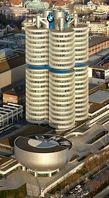 """""""Vierzylinder"""" – BMW-Hauptsitz in München vom Olympiaturm aus gesehen, davor das schüsselförmige BMW-Museum. Bild: Markus Matern  / wikipedia.org"""