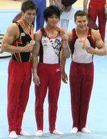 Philipp Boy (links) bei der WM 2010 mit Weltmeister Kōhei Uchimura und Bronzemedaillengewinner Jonathan Horton (USA)