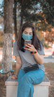 Frau mit Maske und Handy