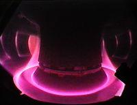 Blick in das viele Millionen Grad heiße Plasma der Fusionsanlage ASDEX Upgrade in Garching. Der Plasmarand wird auf die speziell ausgerüsteten Divertor-Platten am Boden gelenkt. Quelle: Foto: IPP (idw)