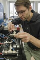Forschung am Wasser-Elektrolyt: Empa-Forscher Ruben-Simon Kühnel schliesst eine Test-Zelle mit der konzentrierten Salzlösung ans experimentelle Ladegerät an. Quelle: Empa (idw)
