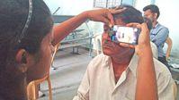 Augen-Screening in Indien: Geschulte Pflegekraft nutzt ein umgerüstetes Smartphone als direkten Augenspiegel Quelle: Foto: privat (idw)