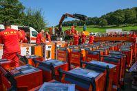 Helferinnen und Helfer der DLRG entpacken und verladen die Bautrockner zum Weitertransport in Ahrweiler.  Bild: DLRG - Deutsche Lebens-Rettungs-Gesellschaft Fotograf: Claudia Dietrich/DLRG