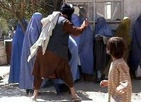 Taliban religious police beating a woman in Kabul on August 26, 2001.
