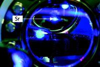 Blick in die Ultrahochvakuumkammer, in der Strontiumatome gekühlt und gespeichert werden. Im oberen Drittel des Fensters ist das blaue Fluoreszenzlicht einer Wolke kalter Strontiumatome zu sehen (das tropfenförmige Gebilde unter dem blau fluoreszierenden Atomstrahl im oberen Teil des Vakuumfensters). Quelle: (Abb.: PTB) (idw)