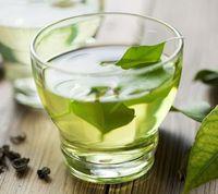 Gefülltes Glas mit wohltuendem grünen Tee.