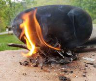 Experiment zur Herstellung von Birkenpech mithilfe von brennender Birkenrinde und einer glatten Oberfläche.