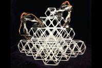Zwei Roboter bauen Gerüst aus Steckelementen.