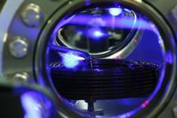 Blick in die Ultrahochvakuumkammer, in der Strontiumatome gekühlt und gespeichert werden. Im oberen Drittel des Fensters ist das blaue Fluoreszenzlicht einer Wolke kalter Strontiumatome zu sehen (das tropfenförmige Gebilde unter dem blau fluoreszierenden Atomstrahl im oberen Teil des Vakuumfensters). Bild: PTB