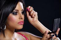 Make-Up: Frau beim Nachschminken mit Wimperntusche.