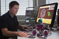 Der Ingenieur Philipp Mittendorfer (TU München) mit dem Roboter Bioloid, der 31 sechseckige Sensormodule verteilt über den ganzen Körper besitzt. Die Sensormodule messen Temperatur, Berührung und Beschleunigung, ähnlich wie die menschliche Haut. Foto: Andreas Heddergott / TU München