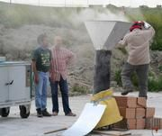So simulieren die Vulkanforscher Eruptionen und pyroklastische Ströme: Die Kanone wurde über einen Einfülltrichter soeben mit heißer Vulkanasche beschickt und steht kurz vor der Eruption. Links im Bild der Elektroofen, in dem die Asche aufgeheizt wurde. Die Forscher sind (von links): Roberto Sulpizio, Franco Balenzano, Pierfrancesco Dellino. Foto: Bernd Zimanowski