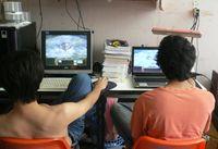 Zwei junge Männer spielen Computerspiele. (Thailand, 2007)