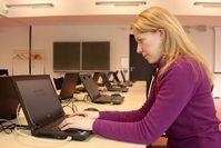 Sandra Fischer, Mitarbeiterin des Servicecenters Lehre der Universität Kassel, bereitet einen Rechner im mobilen E-Klausurcenter für Prüfungen vor.